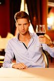 Handsome young man with glass of red wine Stock Photography