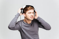 Handsome young man in grey pullover taking off headphones. Over white background Royalty Free Stock Image