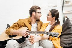handsome young man with guitar flirting with girlfriend royalty free stock photos