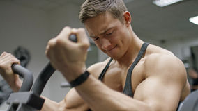 Handsome young man in the gym doing bicep curls on a machine Royalty Free Stock Images