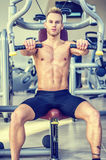 Handsome young man in gym exercising pecs on machine Royalty Free Stock Image