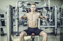 Handsome young man in gym exercising pecs on machine Royalty Free Stock Photo
