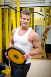 Handsome young man in gym holding weight Royalty Free Stock Photo