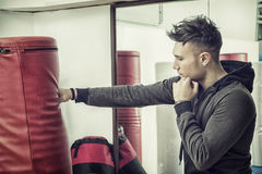 Handsome young man in gym by punching bag Stock Photography