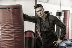Handsome young man in gym by punching bag Stock Image
