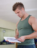 Handsome young man in gym reading workout book Stock Photo