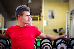 Handsome young man in gym sitting on dumbbells rack Royalty Free Stock Photography