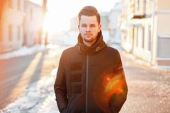 Handsome young man with hair style in a black jacket walking on. The street at sunset royalty free stock photos