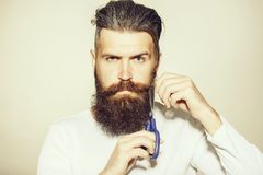 Bearded man with scissors stock image