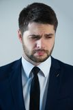 Handsome young man. Half-length portrait of handsome young bearded grieved man wearing white shirt tie and blue jacket thinking about something. Isolated on Stock Photography