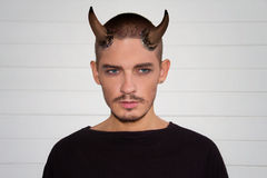 Handsome young man with halloween horns and blue eyes Stock Images