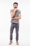 Handsome young man with hand on beard full height smiling Stock Photos