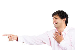 Handsome young man with hand on chest, laughing, and pointing at someone or something Stock Image