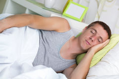 Handsome young man happily sleeping in bed Royalty Free Stock Photos