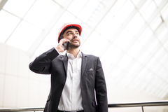 Handsome young man in hardhat holding blueprint and talking on the mobile phone while standing Stock Photo