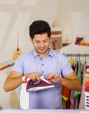 Handsome young Man has an iron cable around his neck trying to use the iron.  Royalty Free Stock Images