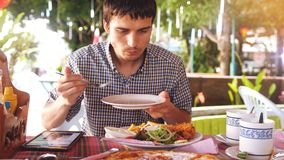 Handsome young man has lunch on the tropical island Royalty Free Stock Photography