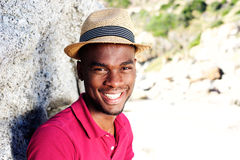 Handsome young man with hat smiling at the beach Stock Photos