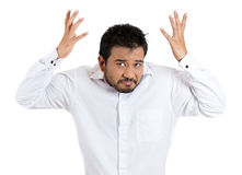 A handsome young man having a bad attitude and temper raising his hands out in the air as if to say who cares Royalty Free Stock Photography