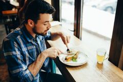 Handsome young man having lunch in cosy restaurant alone. Handsome young man having lunch in cosy restaurant or cafe. He is sitting alone near in front of window stock photos