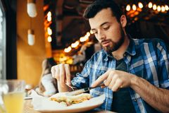 Handsome young man having lunch in elegant restaurant alone. Attractive guy is cutting his tasty sandwich with fork and knife. He is delighted because soon he stock image