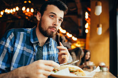 Handsome young man having lunch in elegant restaurant alone. Cute guy is looking at window and tasting small morse of sandwich. He is going to eat all this royalty free stock photo