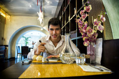 Handsome young man having lunch in elegant restaurant. Alone smiling and looking at camera stock image