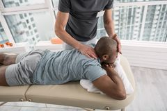 Handsome young man having a massage therapy. Medical center. Handsome young men lying on the medical couch while having a massage therapy stock photos
