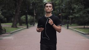 Handsome Young Man in Headphones and Smartphone in his Hand Running in Park Concept Healthy Lifestyle. stock video footage