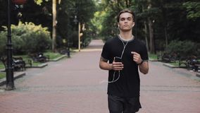 Handsome young man in headphones and smartphone in his hand wearing a jogging suit running in park concept healthy stock video footage