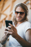 Handsome young man in headphones and sunglasses using smartphone Stock Image