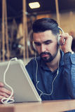 Handsome young man with headphones using tablet computer in coffee shop Royalty Free Stock Image