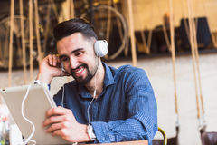 Handsome young man with headphones using tablet computer in coffee shop Royalty Free Stock Photo