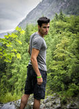Handsome young man hiking in lush green mountain s Stock Image