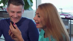 Handsome young man and his beautiful girlfriend using smart phone. Lovely couple laughing and talking, browsing online, watching funny content. Technology stock video footage