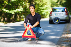 Handsome young man with his car broken down by the roadside Stock Photo