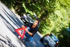 Handsome young man with his car broken down by the roadside Stock Images