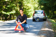 Handsome young man with his car broken down by the roadside Stock Image
