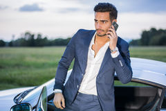 Handsome young man by his car with cell phone Royalty Free Stock Image