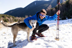 Handsome young man with his dog over winter background. Stock Photography