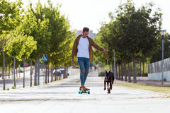 Handsome young man with his dog skateboarding in the park. Royalty Free Stock Photo