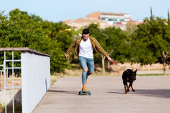 Handsome young man with his dog skateboarding in the park. Royalty Free Stock Images
