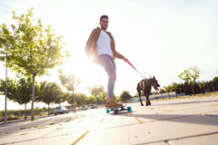 Handsome young man with his dog skateboarding in the park. Stock Photo