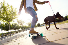 Handsome young man with his dog skateboarding in the park. Royalty Free Stock Photos