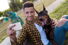 Handsome young man with his dog using mobile phone in the park. Royalty Free Stock Photos