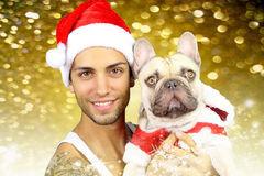 Handsome young man and his french bulldog. Handsome young man and his dog in christmas costume royalty free stock photography