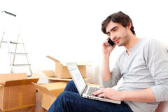 Handsome young man in his new flat ordering on his laptop Stock Image