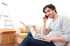 Handsome young man in his new flat ordering on his laptop Stock Images