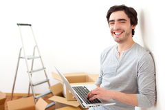 Handsome young man in his new flat using laptop Royalty Free Stock Images