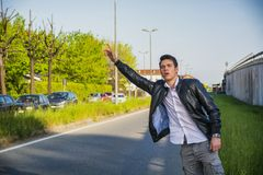 Handsome young man, hitchhiker waiting on roadside Stock Images
